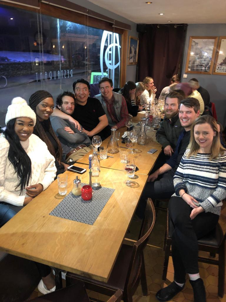 A large group of students pose for a photo over dinner at a restaurant.