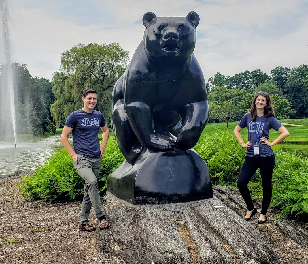 Emily and Taylor standing outside next to a large bear sculpture