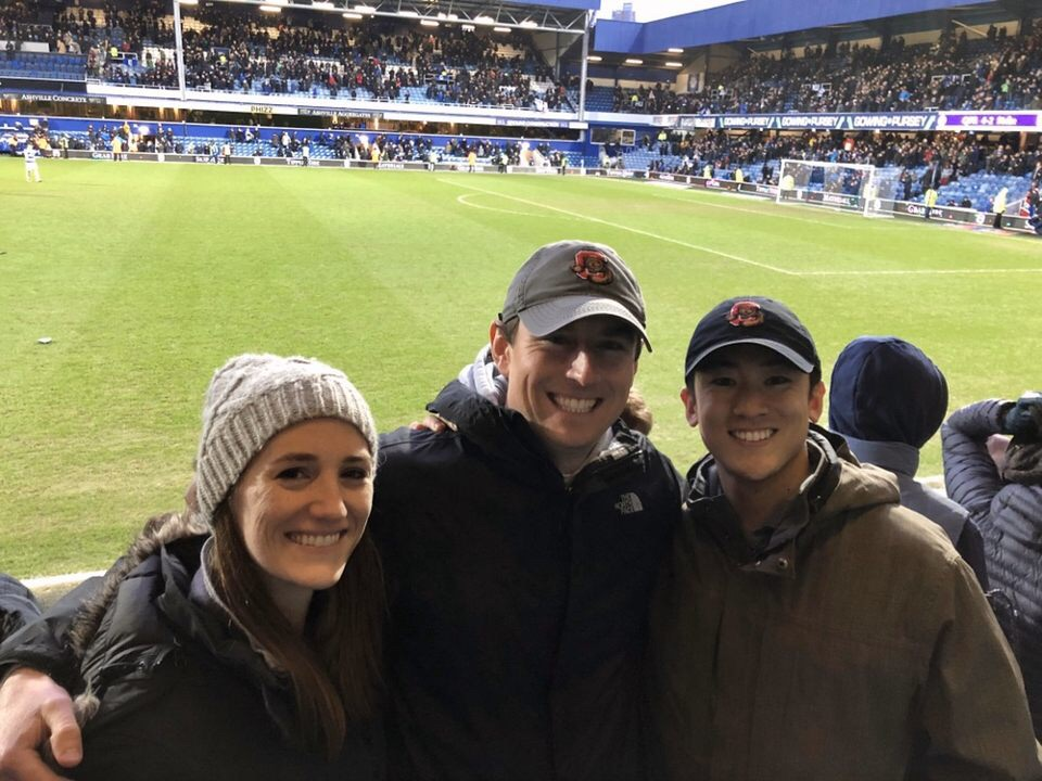 Three students pose for a photo at a soccer match