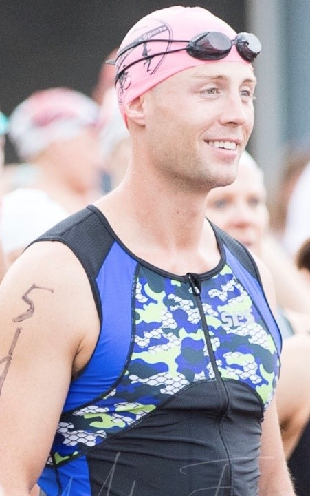 Greg stands in a swim cap among a crowd