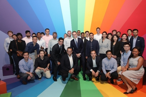 A large group of students stands in front of a rainbow colored wall