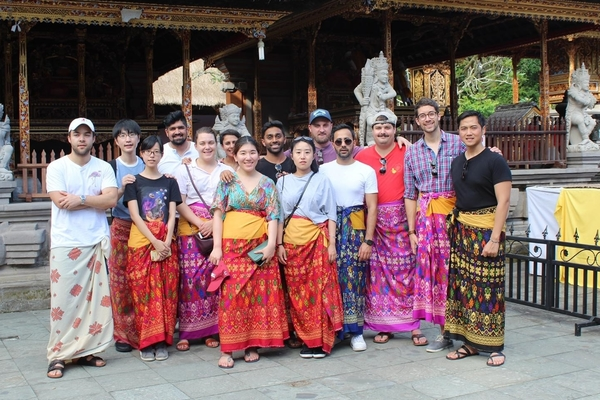Students pose in bright colored traditional clothing