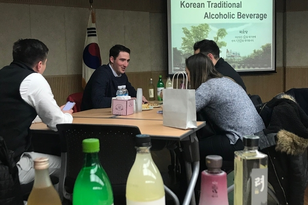 Students sit at a table looking at products