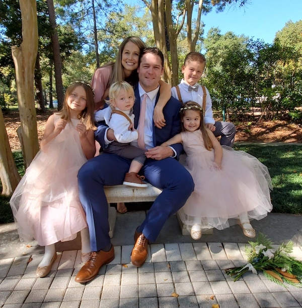 Zach, his wife, and four children pose in formal attire