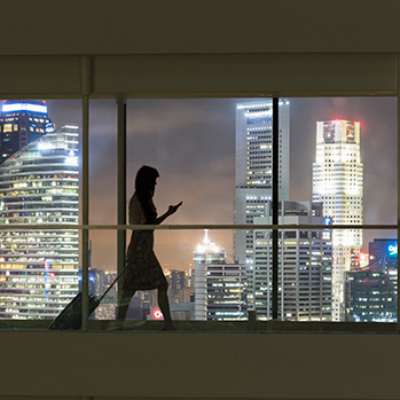 Woman walking while looking at her phone with cityscape in background