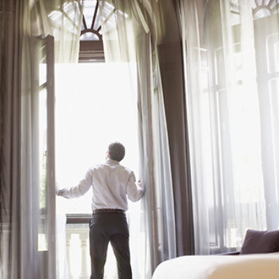 Man looking out hotel room balcony