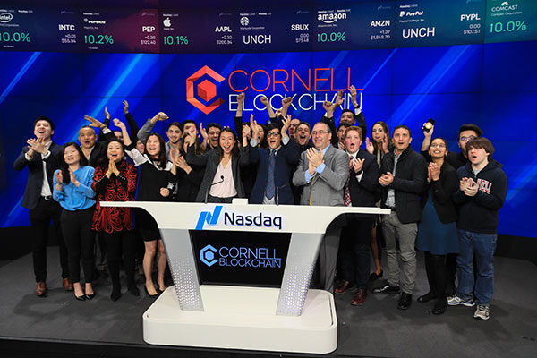 Group photo of Cornell Blockchain members cheering and standing behind the Nasdaq podium at the opening bell, with Cornell Blockchain on the wall behind them and on the podium in front of them
