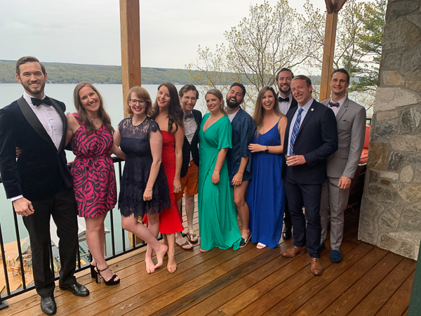 A group of 11 MBA students and partners wearing formal wear pose with a view Lake Cayuga behind them.