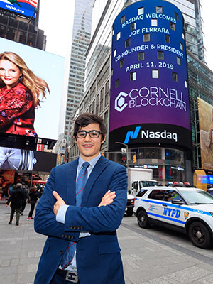 Joe Ferrara '19 standing outside Nasdaq in NYC with her name and Cornell Blockchain on the digital signage