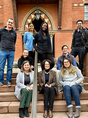 Lourdes Casanova and Anne Miroux and the Emerging Markets Institute's research team, photographed together on the steps of Sage Hall