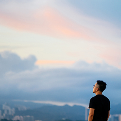 Man on mountain looking out at city below