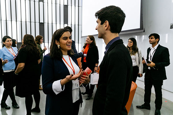 photo of people in business attire mingling and talking to one another in a large, light-filled room