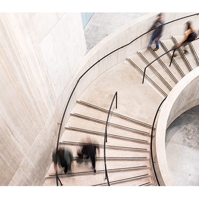 People walking down a curved, concrete staircase