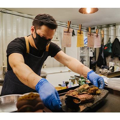 Man in a mask and gloves preparing orders in a kitchen