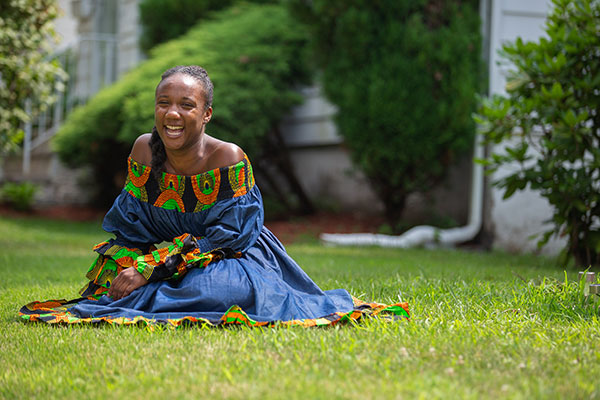 Kamillah Knight sitting on the grass and smiling, wearing a dress