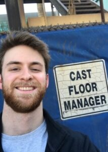 "The author smiles for a selfie next to a sign that reads ""Cast Floor Manager."""