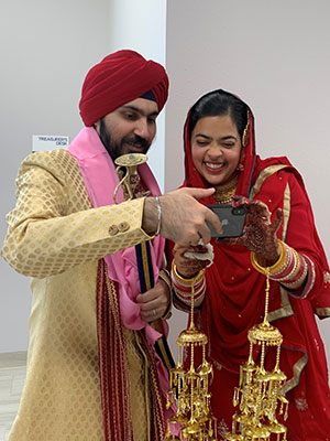 Harkiran Sodhi and her husband in Indian wedding attire holding and o=looking at a cell phone and smiling