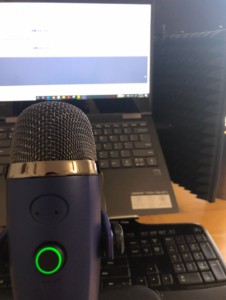 Recording set up for the podcast shows a microphone and computer screen.