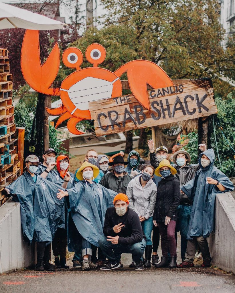 Canlis employees stand infront of a new Canlis sign advertising it as a Crab Shack