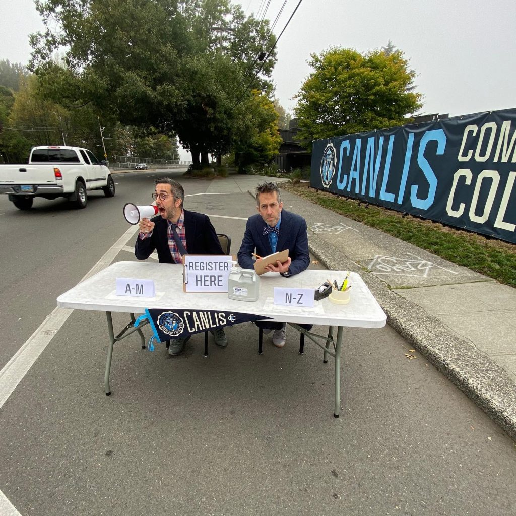 Mark and Brian Canlis sit at a table offering registration for food and beverage classes at the Canlis Community College.