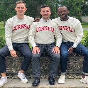 Image of three EMBA Metro NY students sitting on a bench outside, wearing Cornell University sweatshirts