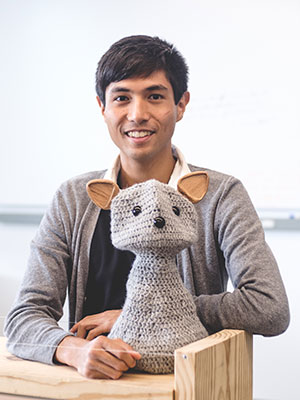 Michael Suguitan sits at a desk behind a crocheted social robot he helped create.