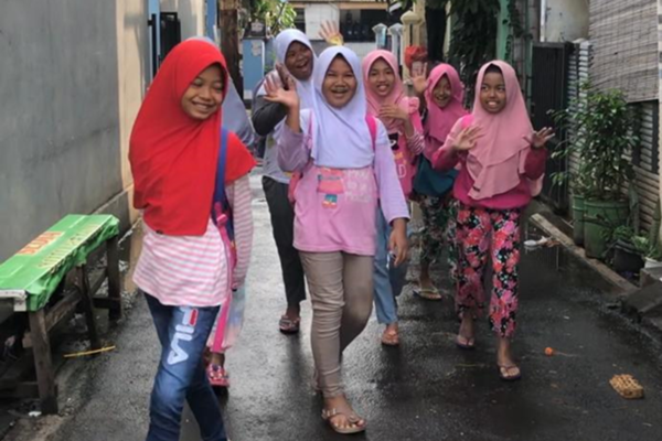 A group of smiley young Indonesian girls wearing pants and hajibs are waving as they walk between buildings