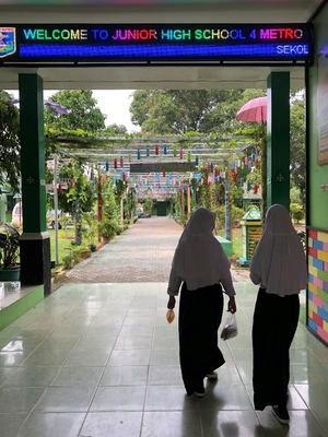 "School entrance and walkway with two girls walking away under a sign that reads, ""Welcome to Junior High School"""