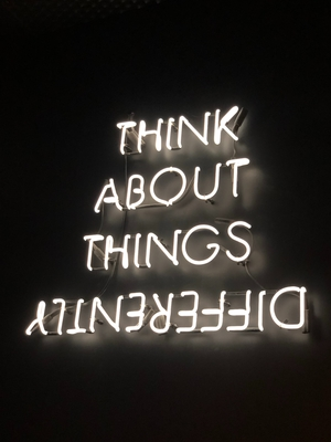 """Neon sign with this text: """"think about things differently"""" - """"differently appears backwards"""
