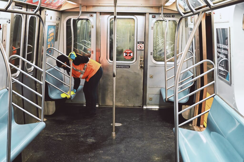 Essential worker in PPE sanitizing a subway car