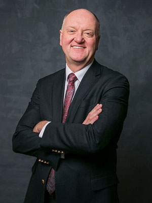portrait of Andrew Karolyi standing with folded arms