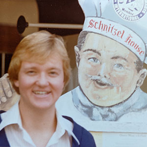 """1981 photo of Andrew Karolyi standing in front of a sign depicting a chef in a chef's hat with """"Schnitzel House written on it"""