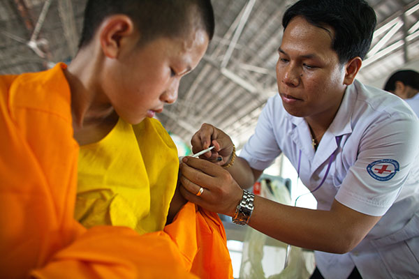 Clinician providing a shot to a young boy
