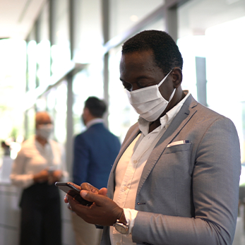 Man in mask looking at mobile device