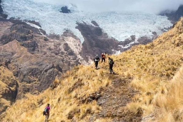 Travelers hiking in a steep, treeless, mountainous landscape
