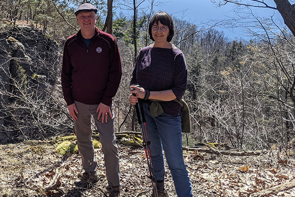 Andrew and Anne Karolyi on a trail in the woods near Ithaca