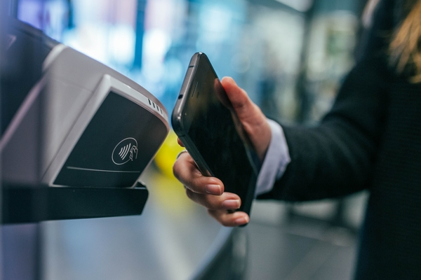 A person uses a cell phone at a payment terminal to make a wireless payment.