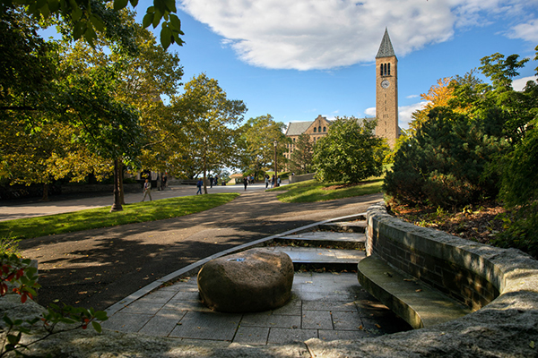 a stone bench in the foreground leading to Hoh Plaza walkway and McGraw Tower in the background