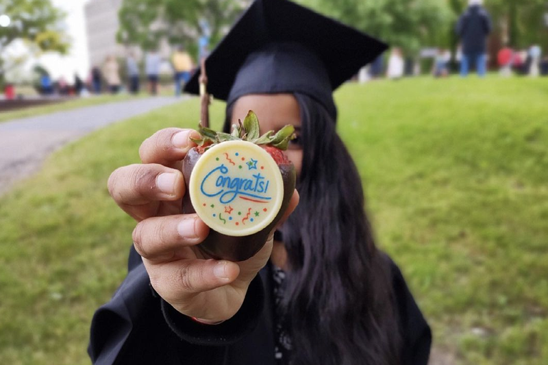 graduate holding strawberry pastry that says congrats