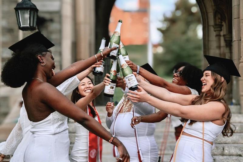 SHA graduates toasting with bottles of sparkling cider