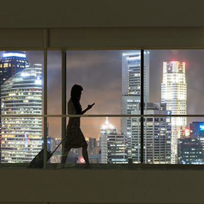 Woman walking through hallway with cityscape outside