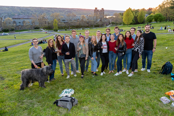 group of students posing for a photo on libe slope at dusk