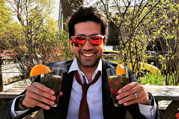 ankit Dhawan sitting outside, grinning, wearing sunglasses, in warm weather and holding up two glasses of a beverage with orange slices on the rims