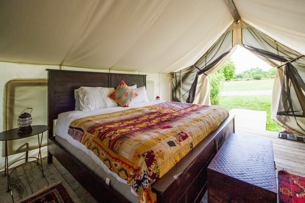 Inside a typical Firelight Camps tent featuring a large bed with a colorful bedspread, wood floor, chest, and table and a camping lantern.