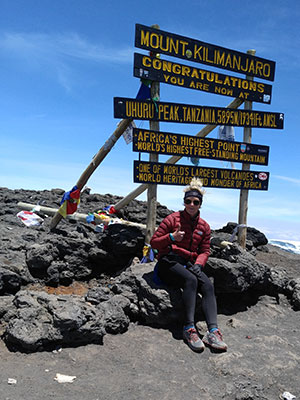 Anissa Buckley sitting in front of a sign that reads: Mount Kilimanjaro, Congratulations you are now at Uhuru Peak, Tanzania, 5895 M / 19341 Ft Africa's highest point, World's highest free-standing mountain