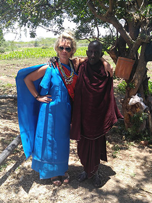 Anissa Buckley standing under a shady tree, arm-in-arm with a Maasai tribe member