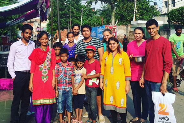 Samay Bansal surrounded by a group of adults and children standing near a kiosk on a city street in Ludhiana, Punjab, India