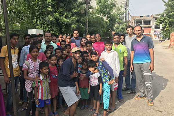 Samay Bansal surrounded by a group of children and adults on a street in Ludhiana,