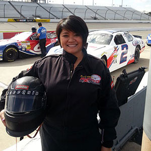 Gage Javier standing and hold a helmet at a race track with race cars in the background