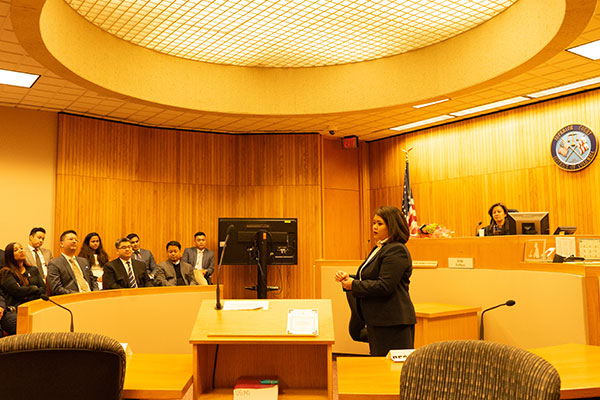 Gage Javier standing and addressing men and women seated in a court room